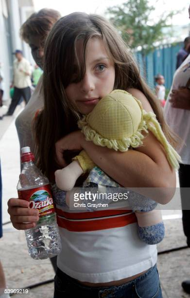 Amanda Malloy from Metairie Louisiana hugs a stuffed doll given to her by a Red Cross volunteer before entering a shelter at the River Center on...
