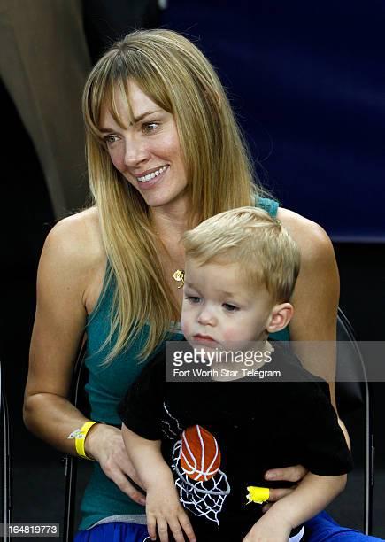 Amanda Marcum Enfield wife of Florida Gulf Coast head coach Andy Enfield watches practice with their son Marcum at Cowboys Stadium in Arlington Texas...