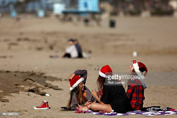 BEACH CA Amanda Mattes Tori Carlos and Lilly Mattes all of Huntington Beach enjoy Christmas morning on the beach where skies were mostly clear and...