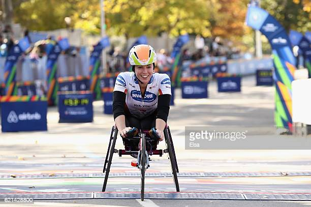 Amanda McGrory of the United States smiles as she crosses the finish line to finish third in the Pro Women's Wheelchair Division during the 2016 TCS...