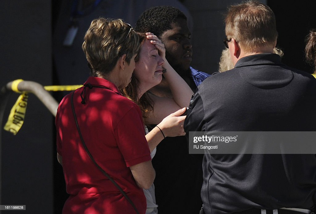 Amanda Medek, second from the left, who is looking for her sister Micayla, is overcome with emotion outside Gateway High School, Friday July 20, 2012, in Aurora. Micayla is still missing after 50 people were shot 12 fatally early Friday inside an Aurora movie theater during a premiere showing of the new Batman movie, were taken to the high school by bus to be questioned by police. RJ Sangosti, The Denver Post