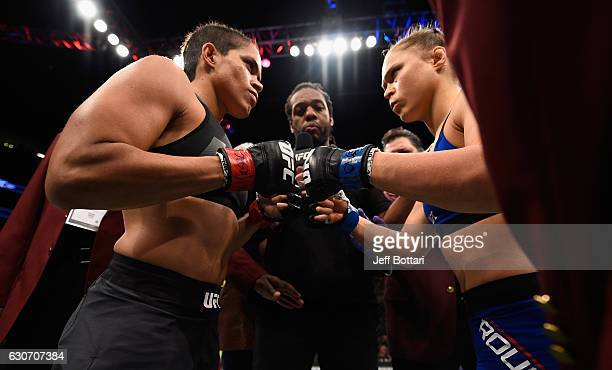 Amanda Nunes of Brazil and Ronda Rousey touch gloves in their UFC women's bantamweight championship bout during the UFC 207 event at TMobile Arena on...