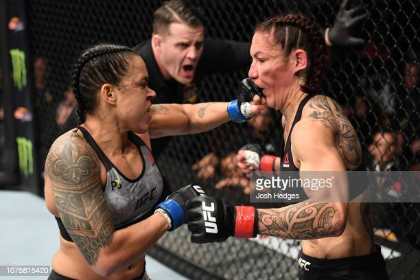 Amanda Nunes of Brazil punches Cris Cyborg of Brazil in their women's featherweight bout during the UFC 232 event inside The Forum on December 29...