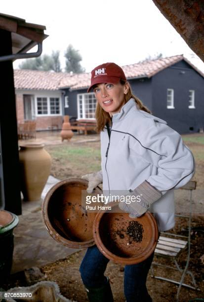 HILLS HOLLYWOOD CA DECEMBER 14 Amanda Pays English actress model works in the garden of the first home she purchased renovated and decorated with her...