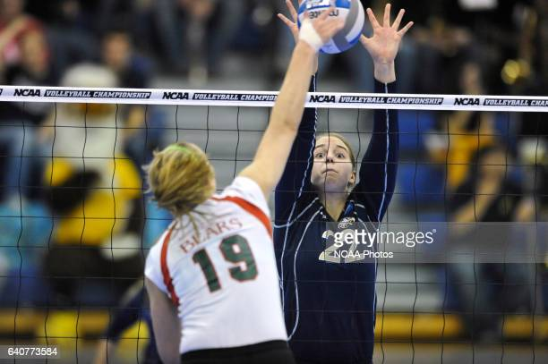 Amanda Schmidt of Juniata jumps to block a ball hit by Lauren Budde of Washington University during the Division III Women's Volleyball Championship...