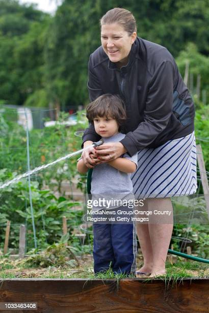 Amanda Sitala helps her 3yearold son Elisaia water the vegetables in the Garden Grove Community GardenHer church Seventhday Adventist grows...