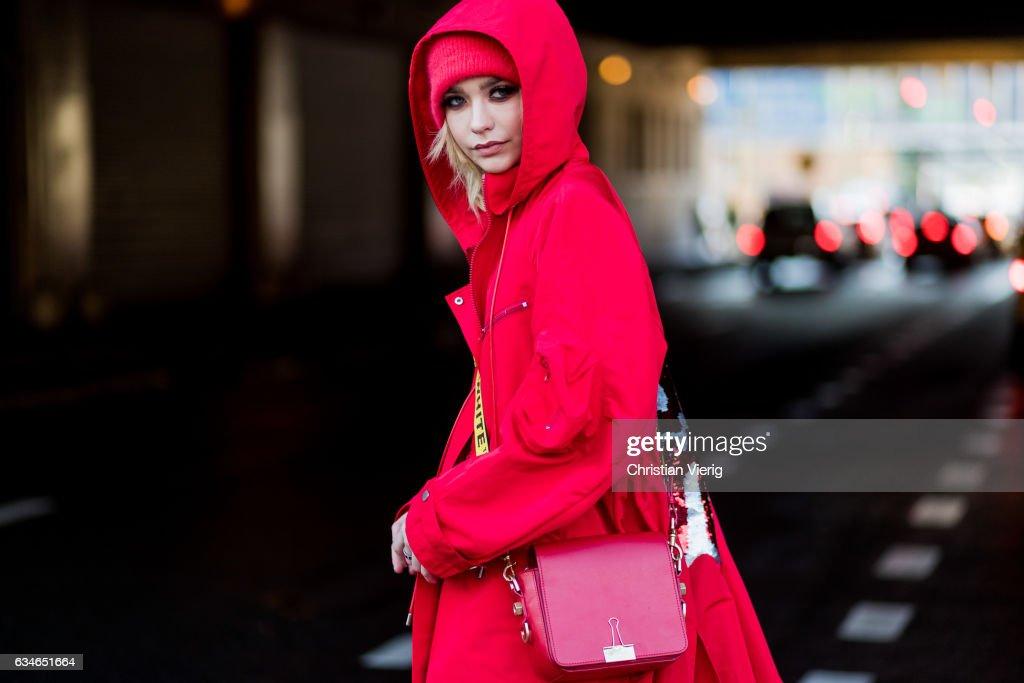 Amanda Steele wearing a red hooded coat, red beanie, Off White bag outside Cushnie et Ochs on February 10, 2017 in New York City.