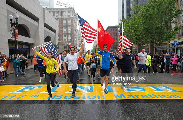 Amanda Watters Mike Ross Kyle Shade and MIT shirt Andrew Truco carry flags as they cross the Boston Marathon finish line on Boylston Street during...