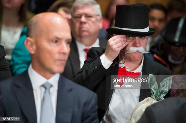 Amanda Werner who is dressed as Monopoly's Rich Uncle Pennybags sits behind Richard Smith left CEO of Equifax during a Senate Banking Housing and...
