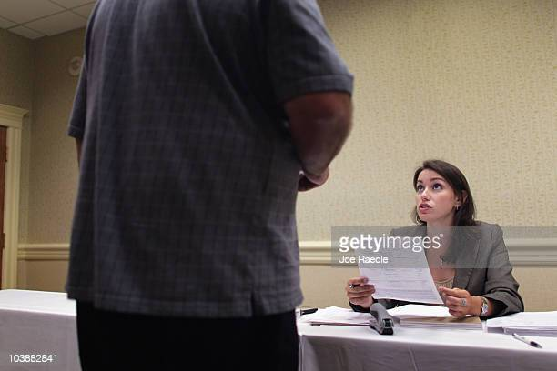 Amanda Winchip District Manager for grocery retailer ALDI takes an application from a person looking to fill a job opening in one of the new stores...