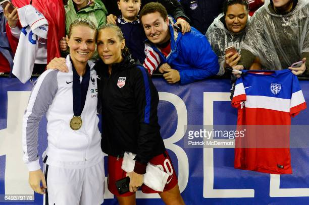 Amandine Henry of France and Allie Long of United States of America pose for a photo after France defeated the United States of America 30 to win the...