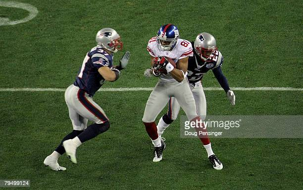 Amani Toomer of the New York Giants catches a ball for a first down against Rodney Harrison and Asante Samuel of the New England Patriots during...