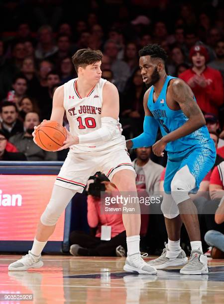 Amar Alibegovic of the St John's Red Storm is defended by Jessie Govan of the Georgetown Hoyas during an NCAA men's basketball game at Madison Square...