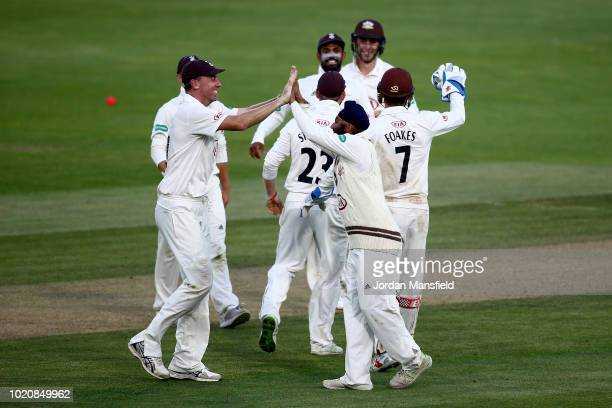 Amar Virdi and Will Jacks of Surrey celebrate with their teammates after dismissing Shivnarine Chanderpaul of Lancashire during day three of the...