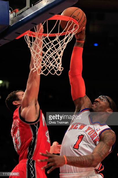 Amar'e Stoudemire of the New York Knicks shoots over Kris Humphries of the New Jersey Nets at Madison Square Garden on March 30 2011 in New York City...
