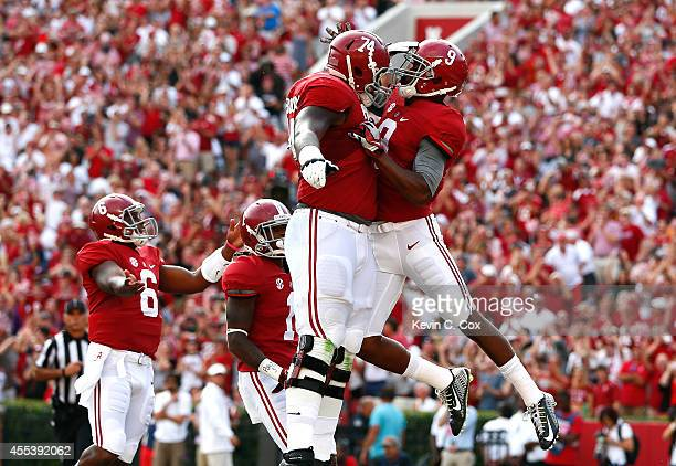 Amari Cooper of the Alabama Crimson Tide celebrates scoring a touchdown against Southern Miss Golden Eagles with Cam Robinson of the Alabama Crimson...