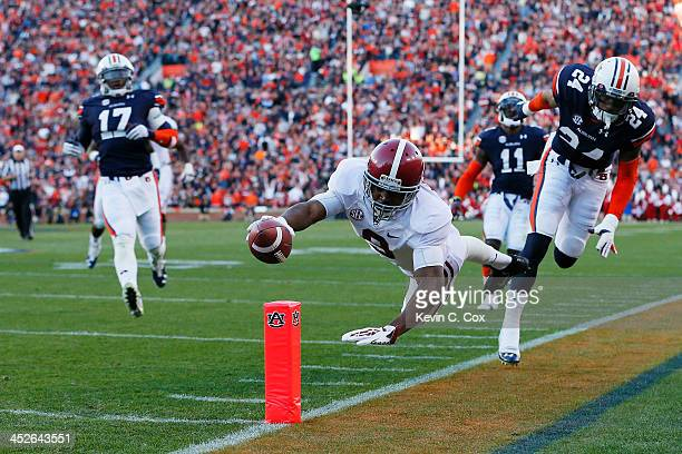 Amari Cooper of the Alabama Crimson Tide rushes for 28 yards in the second quarter for a first down against the defense of Ryan Smith of the Auburn...