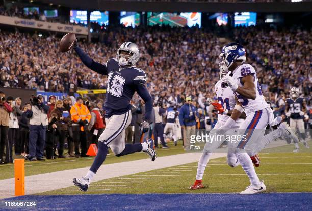 Amari Cooper of the Dallas Cowboys celebrates his touchdown in the fourth quarter as Corey Ballentine and Michael Thomas of the New York Giants...