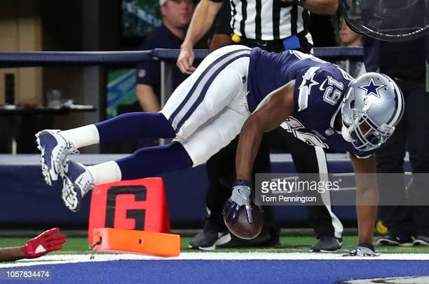 Amari Cooper of the Dallas Cowboys falls into the sideline after scoring a touchdown against the Tennessee Titans in the first quarter at ATT Stadium...
