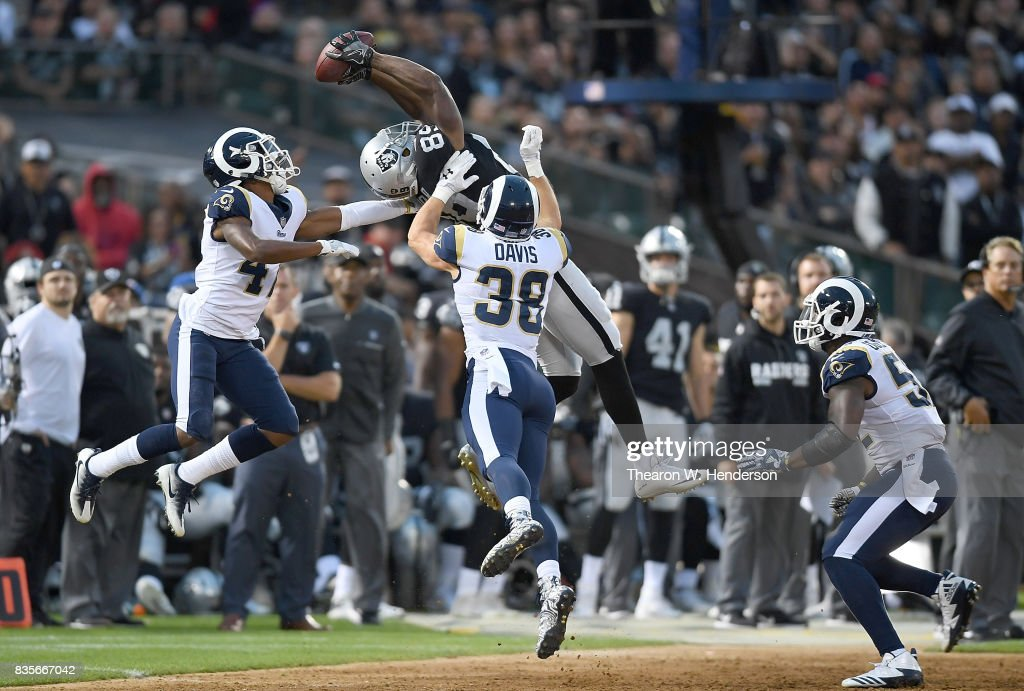 Amari Cooper #89 of the Oakland Raiders catches a thirty one yard pass over Kevin Peterson #47 and Cody Davis #38 of the Los Angeles Rams during the second quarter of their preseason NFL football game at Oakland-Alameda County Coliseum on August 19, 2017 in Oakland, California.
