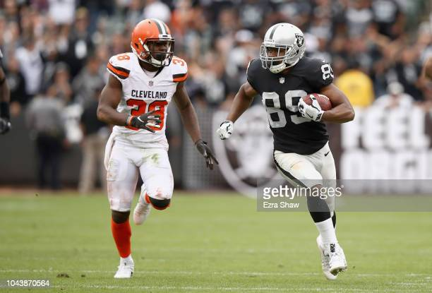 Amari Cooper of the Oakland Raiders tries to outrun TJ Carrie of the Cleveland Browns at OaklandAlameda County Coliseum on September 30 2018 in...