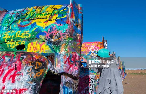 Amarillo Texas famous Cadillac Ranch teen spraying paint off of Route 66 old Cadillacs buried in ground on Route 66