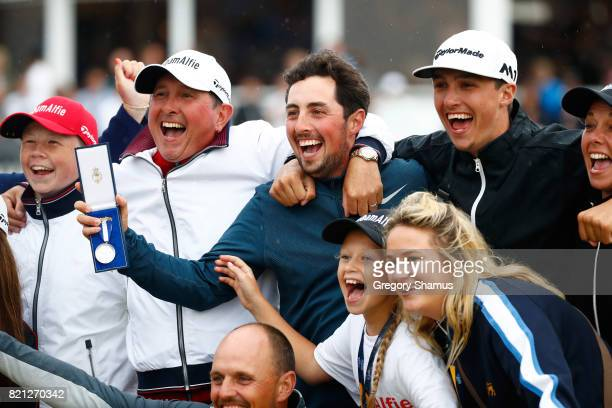 Amateur Alfie Plant of England holds the Silver Medal awarded to highest placed amateur celebrates with his family and friends on the 18th green...