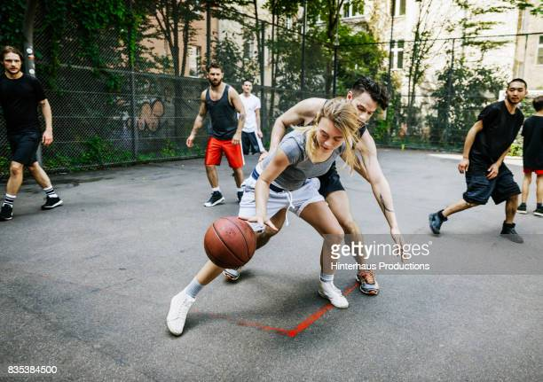 amateur athlete defending her position during basketball game - sportmannschaft stock-fotos und bilder