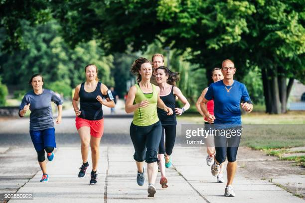 amateur athlete group jogging alongside each other - jogging stock photos and pictures