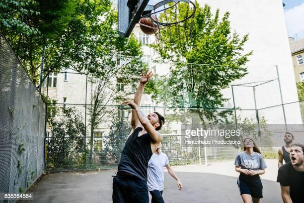 amateur basketball player leaps to make shot for his team - mannschafts wettbewerb stock-fotos und bilder