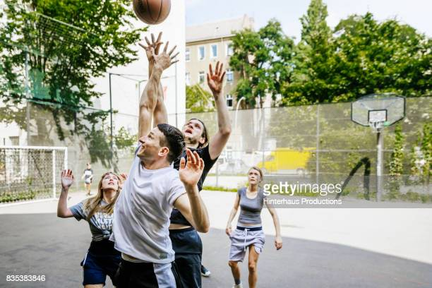 Amateur Basketball Players Competing For Control Of The Ball