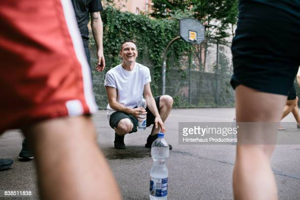 amateur basketball players take break from the game for refreshments - leisure equipment stock pictures, royalty-free photos & images
