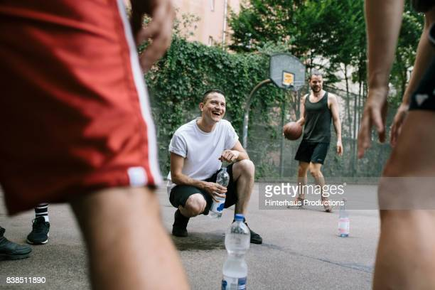 Amateur Basketball Players Take Break To Have A Drink And Recover