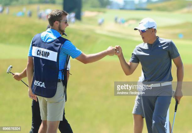 Amateur Cameron Champ of the United States and caddie Jake Goodman celebrate after finishing on the 18th green during the second round of the 2017 US...