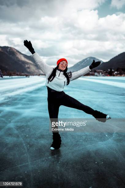 amateur figure skater enjoying skating on a frozen lake in the winter - vertical stock pictures, royalty-free photos & images