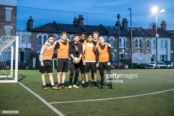 amateur football team portrait at night on urban floodlit pitch - amateur stock pictures, royalty-free photos & images