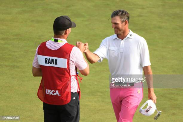 Amateur Garrett Rank of the United States shakes hands with caddie Kyle Rank on the 18th green during the second round of the 2018 US Open at...