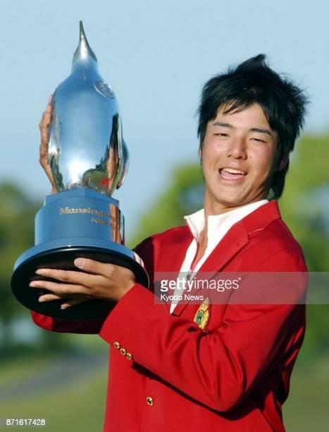 Amateur golfer Ryo Ishikawa poses for photographs with the trophy after winning the Munsingwear Open KBS Cup at Tojigaoka Marinehills Golf Club on...