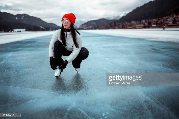 amateur ice skater tying her skate laces while on the ice outside - figure skating stock pictures, royalty-free photos & images