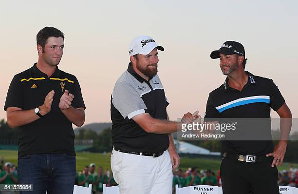 Amateur Jon Rahm of Spain Shane Lowry of Ireland and Scott Piercy of the United States shake hands on the 18th green following the final round of the...