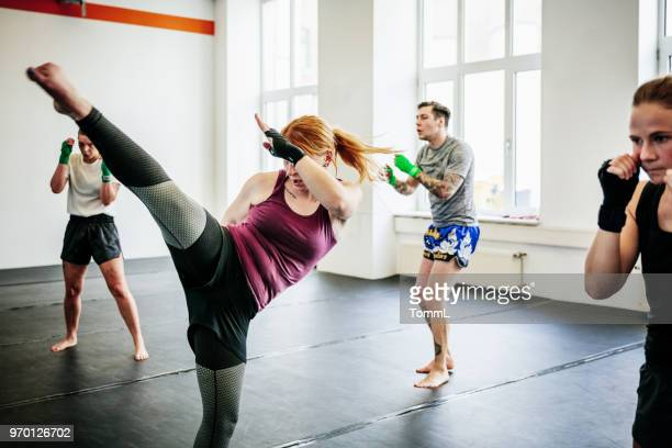 amateur kickboxers performing various kicks together - kickboxing stock pictures, royalty-free photos & images