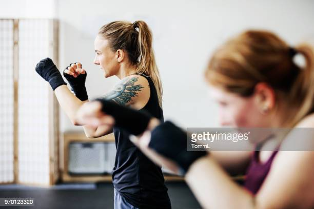 amateur kickboxers shadow boxing together - boxing stock pictures, royalty-free photos & images