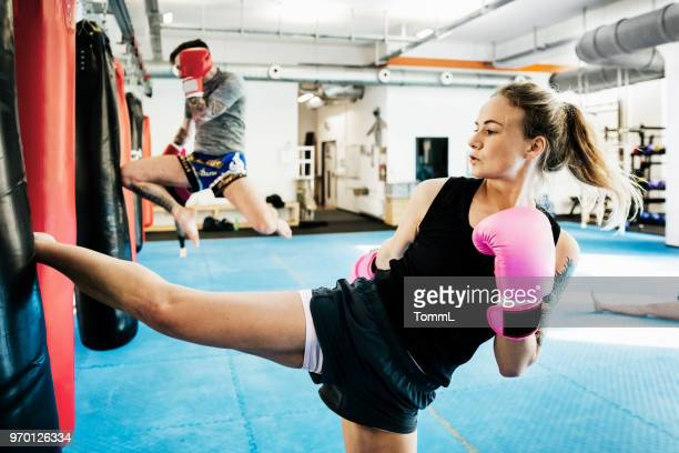 amateur kickboxers training on heavy bags - muay thai imagens e fotografias de stock