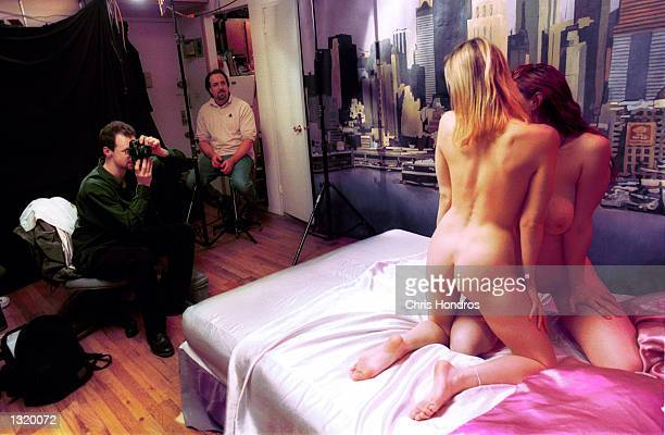 Amateur models are photographed by artist and adult filmmaker Irvin Bomb left before shooting a pornographic video December 15 2000 in New York...
