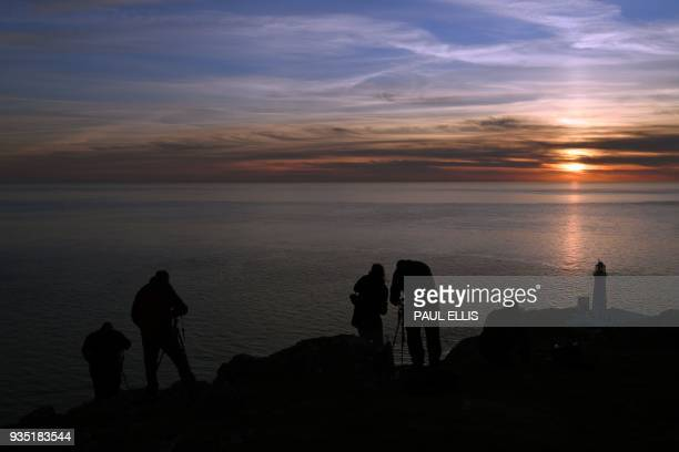 Amateur photographers stand on the rocks to capture the sunset over the Irish Sea beyond the South Stack lighthouse on Anglesey in north Wales on...