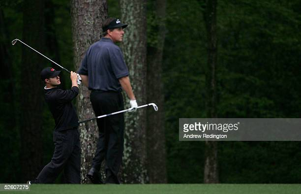 Amateur Ryan Moore hits a shot on the 11th hole as Phil Mickelson looks on during round two of The Masters at the Augusta National Golf Club on April...