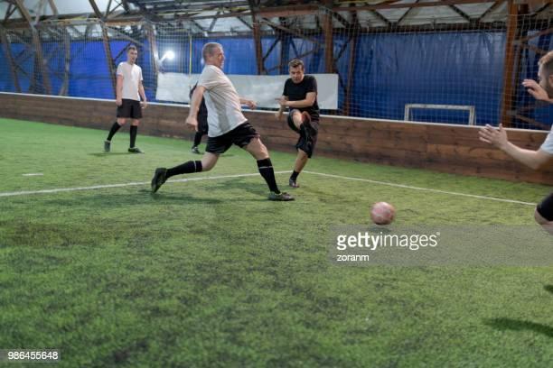 amateur speler schoppen voetbal - aanvaller stockfoto's en -beelden