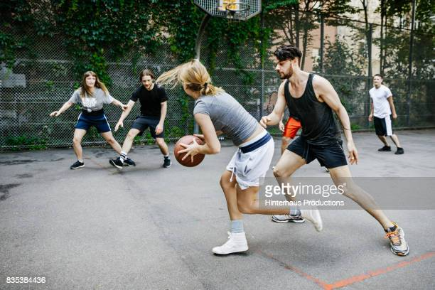 amateur sportswoman preparing to pass to teammate during basketball game - basketbal teamsport stockfoto's en -beelden