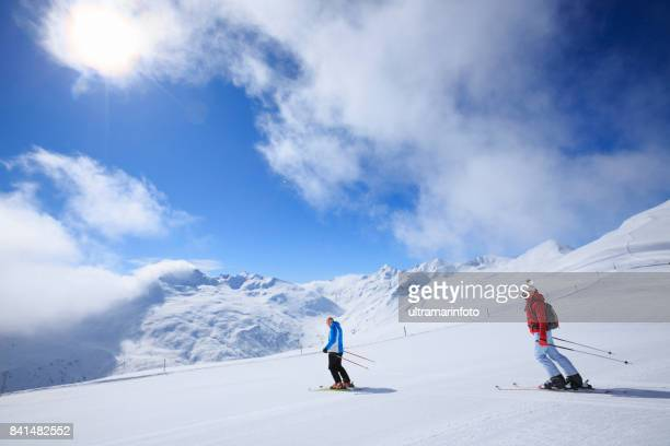 Amateur Winter Sports  alpine skiing. Best friends men and women, snow skiers  enjoying on sunny ski resorts.  High mountain snowy landscape. Livigno mountain range, Alps. It is located in the Italiy.