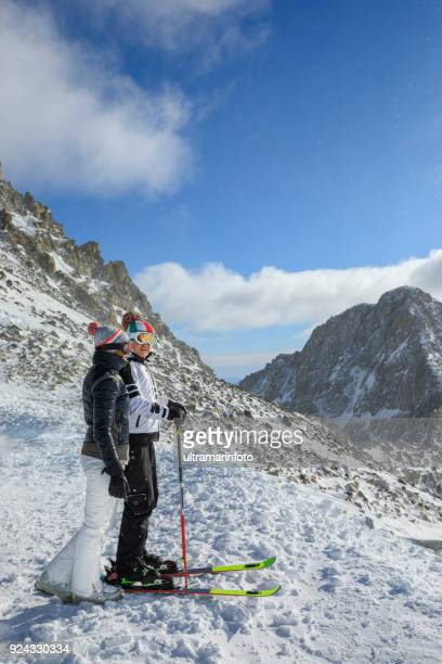 amateur winter sports  alpine skiing.  couple best friends men and women, snow skiers  enjoying on sunny ski resorts.  high mountain snowy landscape.  italian alps mountain of the dolomites  italy, europe. - winter sports event stock pictures, royalty-free photos & images